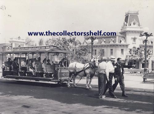 Walt Disney and Joe Fowler walk by a trolley on Main St. in 1955